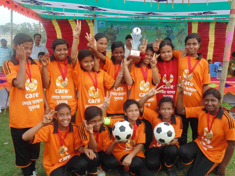 A team of smiling girls in football shirts