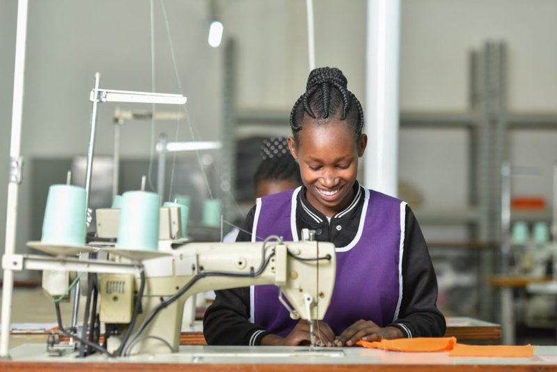A young woman smiles as she learns to use an industrial sewing machine.