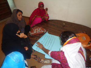 Saima talking with women in the community about the practice of child marriage.