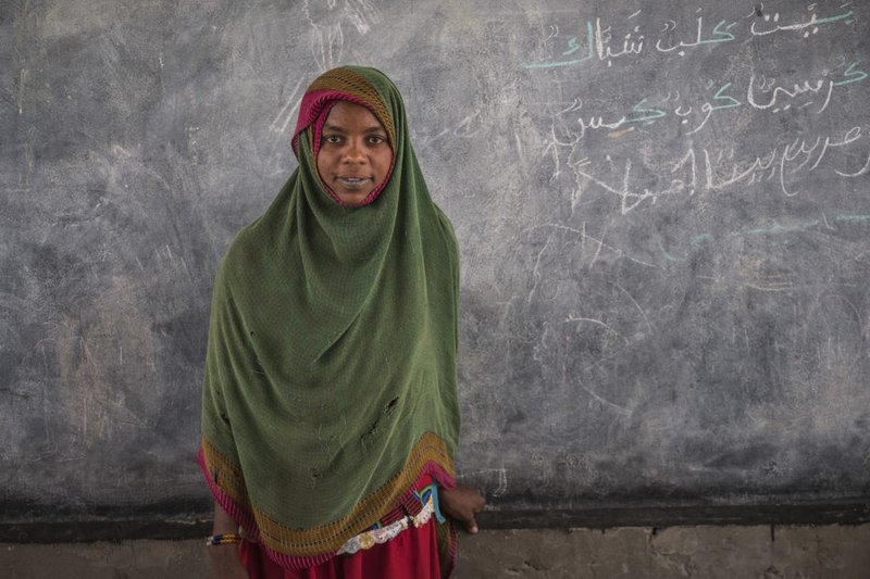 An adolescent girl stands in a classroom, in front of a blackboard.