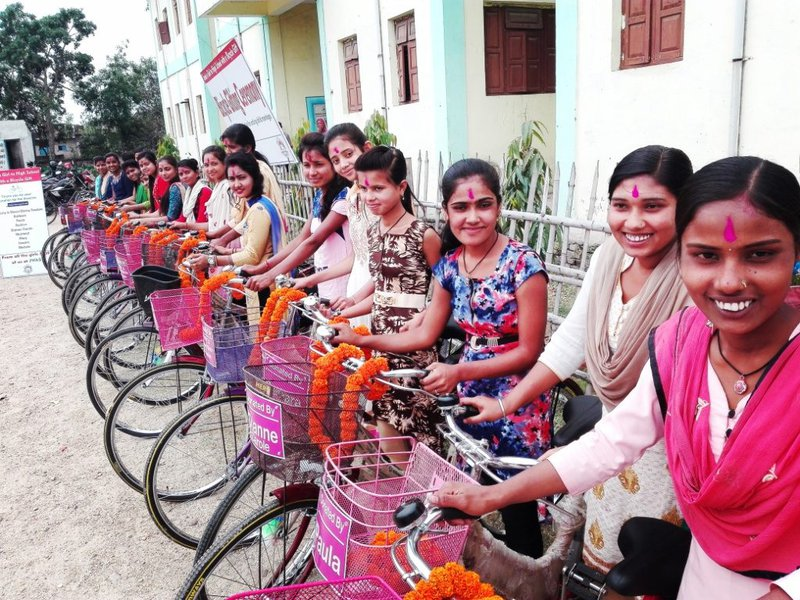 A group of smiling girls pose with their bicycles, at a bicycle gifting ceremony in Nepal.