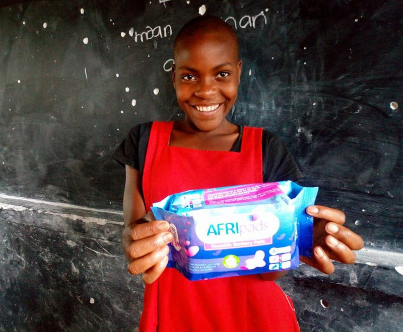 A young girl smiles, showing the reusable sanitary pads that will help her stay in school.