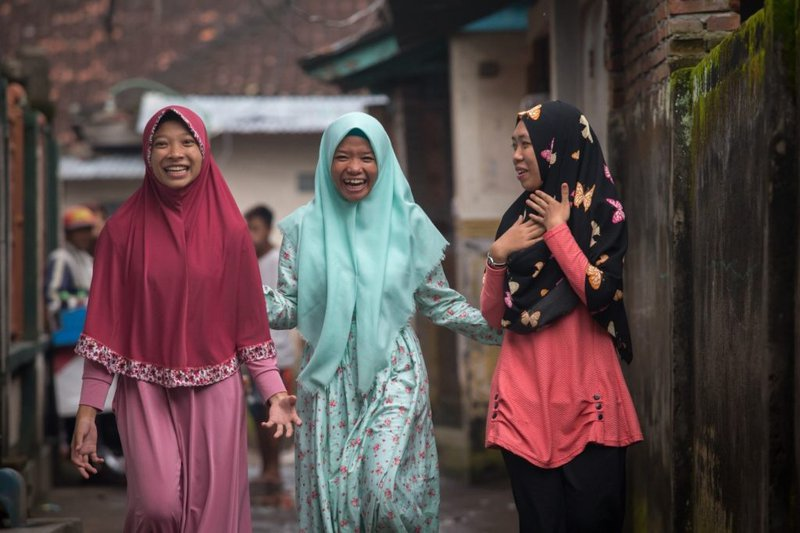 Three youth activists walk, smiling and laughing.