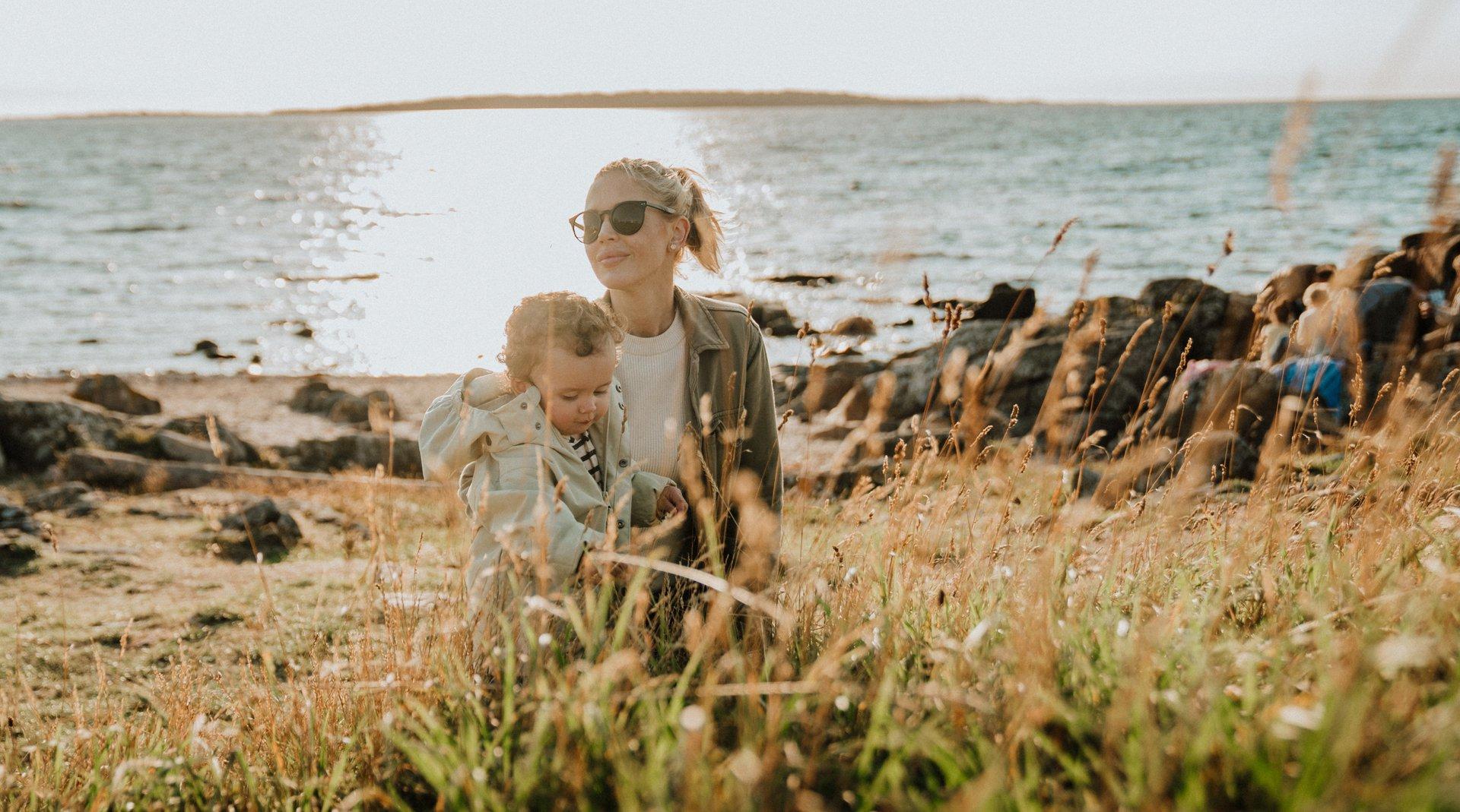 Kvinna med barn på stranden i Båstad