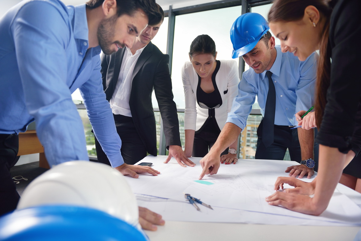 business people group on meeting and presentation  in bright modern office with construction engineer architect and worker looking building model and blueprint planbleprint plans