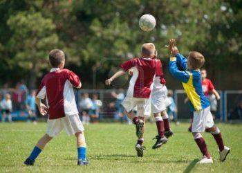 -ragazzini-che-giocano-a-calcio-sul-campo-sportivo