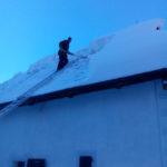 Odstraňovanie snehu z ostrechy na Vyšnokubínksje kúrii v Zuberci